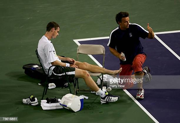 Andy Murray of Great Britain receives treatment from the trainer after injuring his ankle in the second set of his quarterfinal match against Tommy...