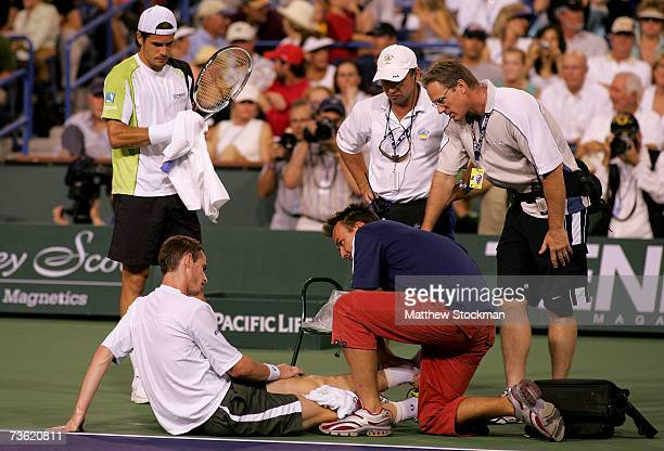 Andy Murray of Great Britain receives treatment from the trainer after injuring his ankle in the second set of his quarterfinal match as his opponent...