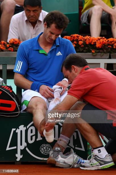 Andy Murray of Great Britain receives treatment on his injured ankle during the men's singles round four match between Andy Murray of Great Britain...