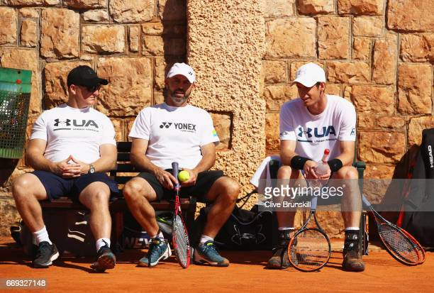 Andy Murray of Great Britain relaxes at the change of ends with his coach Jamie Delgado and physical fitness trainer Matt Little during his practice...