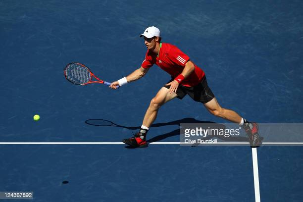 Andy Murray of Great Britain returns a shot against John Isner of the United States during Day Twelve of the 2011 US Open at the USTA Billie Jean...