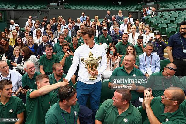 Andy Murray of Great Britain revisits centre court and meets members of the ground staff at Wimbledon on July 11 2016 in London England