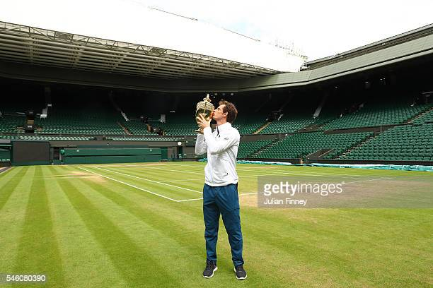 Andy Murray of Great Britain revisits centre court as he kisses the trophy at Wimbledon on July 11 2016 in London England