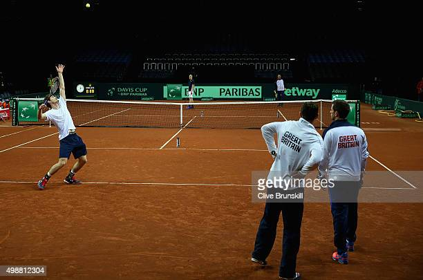 Andy Murray of Great Britain serves watched by his team captain Leon Smith during a practice session ahead of the start of the Davis Cup Final at...