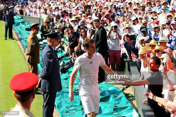 Andy Murray of Great Britain shakes hands with a fan as he makes his way up to his player's box following his victory in the Gentlemen's Singles...