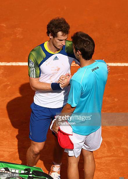 Andy Murray of Great Britain shakes the hand of his competitor after retiring from his second round match against Marcel Granollers of Spain on day...