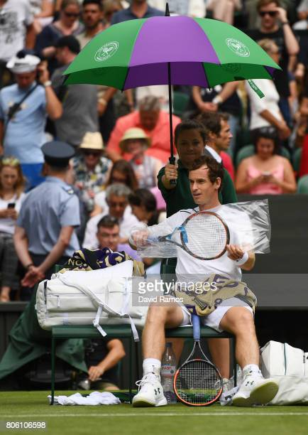 Andy Murray of Great Britain shelters from the rain during the Gentlemen's Singles first round match against Alexander Bublik of Kazakhstan on day...
