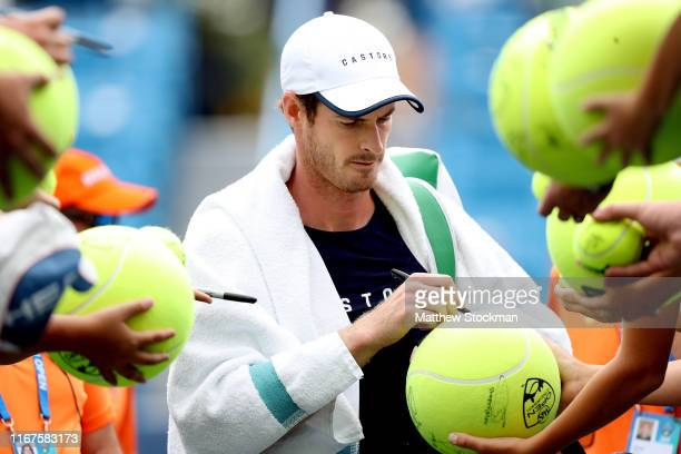 Andy Murray of Great Britain signs autographs after a training session on center court during the Western Southern Open at Lindner Family Tennis...