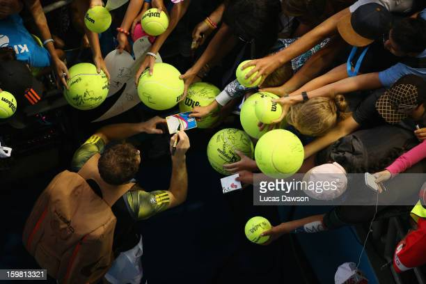 Andy Murray of Great Britain signs autographs after winning his fourth round match against Gilles Simon of France during day eight of the 2013...