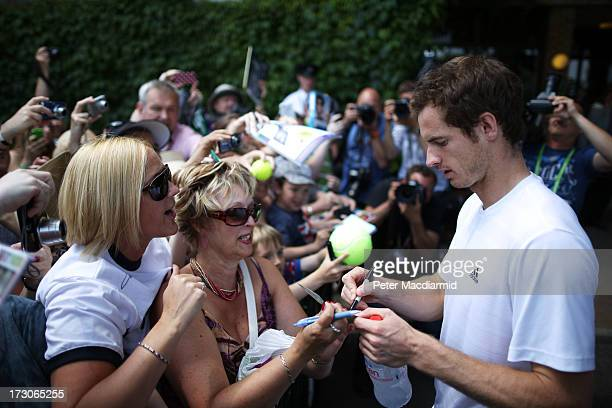 Andy Murray of Great Britain signs autographs for fans after a practice session on day twelve of the Wimbledon Lawn Tennis Championships at the All...