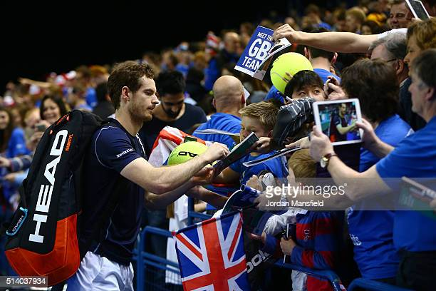 Andy Murray of Great Britain signs autographs for the fans following victory during the singles match against Kei Nishikori of Japan on day three of...