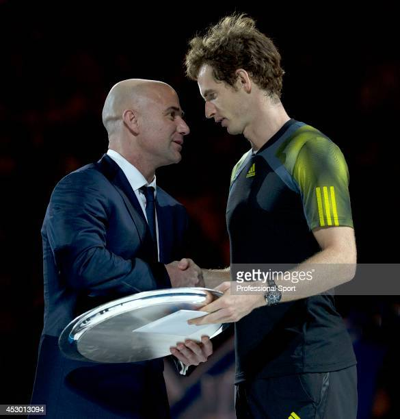 Andy Murray of Great Britain speaks to Andre Agassi after losing his men's final match against Novak Djokovic of Serbia during day fourteen of the...