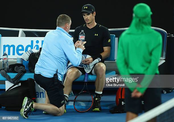 Andy Murray of Great Britain speaks with the physio at the change of ends after injuring his ankle after he fell over in his second round match...