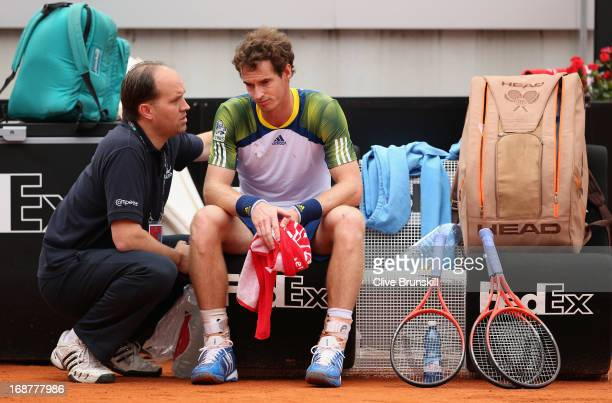 Andy Murray of Great Britain speaks with trainer Clay Sniteman prior to taking an injury timeout against Marcel Granollers of Spain in their second...