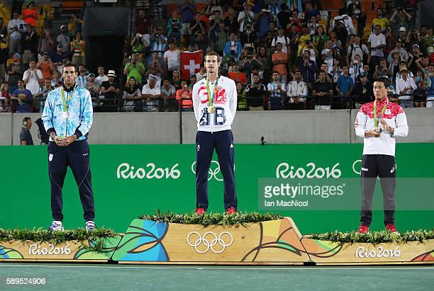 Andy Murray of Great Britain stands on the podium with Juan Martin del Potro of Argentina and Kei Nishikori of Japan after the Men's singles final at...