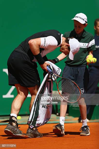 Andy Murray of Great Britain stumbles over the feet of a ball boy during his match against Benoit Paire of France during day five of the Monte Carlo...