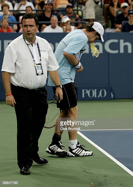 Andy Murray of Great Britain vomits for the second time during the last set of his match against Andrei Pavel of Romania as Line Official Mike...