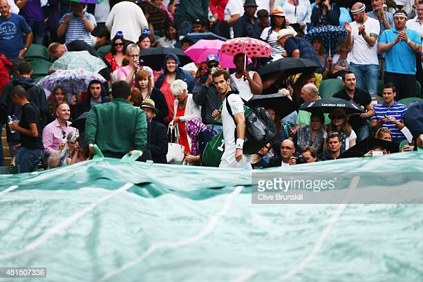 Andy Murray of Great Britain walks off as rain delays play on centre court during his Gentlemen's Singles fourth round match against Kevin Anderson...