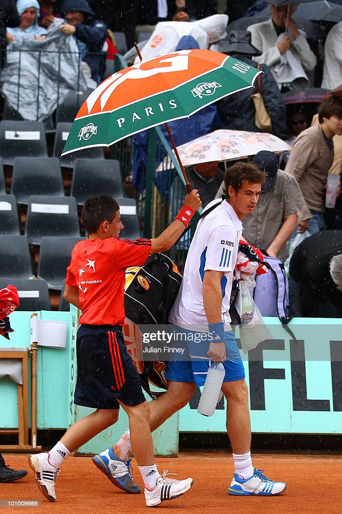Andy Murray of Great Britain walks off under an umbrella after play was suspended due to rain during the men's singles second round match between Andy Murray of Great Britain and Juan Ignacio Chela of Argentina on day five of the French Open at Roland Garros on May 27, 2010 in Paris, France.
