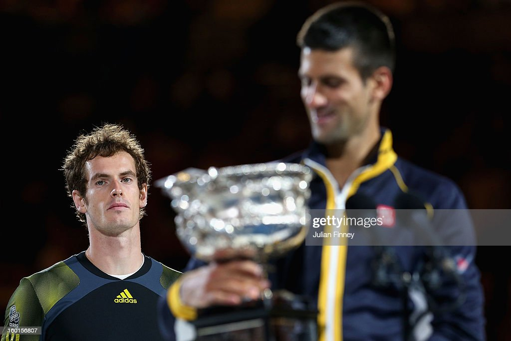 Andy Murray of Great Britain (L) watches Novak Djokovic of Serbia hold the Norman Brookes Challenge Cup after Djokovic won their men's final match during day fourteen of the 2013 Australian Open at Melbourne Park on January 27, 2013 in Melbourne, Australia.