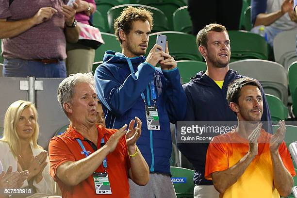 Andy Murray of Great Britain watches on as Jamie Murray of Great Britain and Bruno Soares of Brazil celebrate winning their Men's Doubles Final match...