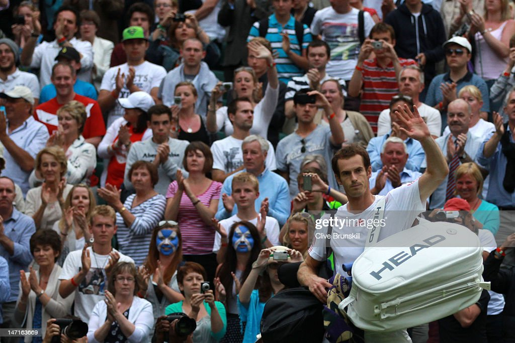 Andy Murray of Great Britain waves to the crowd after winning his Gentlemen's Singles first round match against Nikolay Davydenko of Russia on day two of the Wimbledon Lawn Tennis Championships at the All England Lawn Tennis and Croquet Club on June 26, 2012 in London, England.