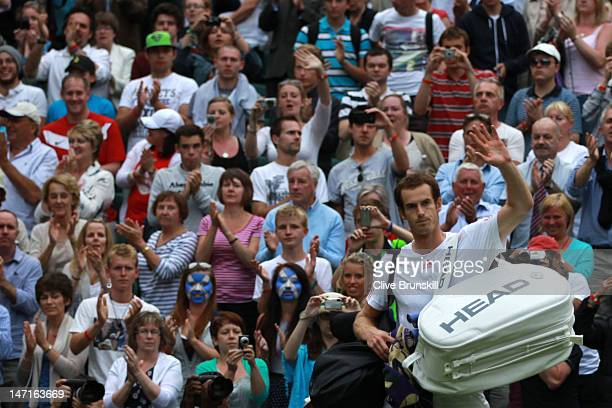 Andy Murray of Great Britain waves to the crowd after winning his Gentlemen's Singles first round match against Nikolay Davydenko of Russia on day...