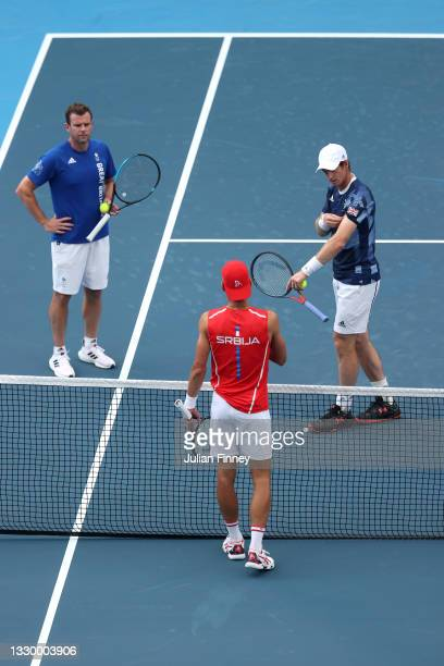 Andy Murray of Team Great Britain and Novak Djokovic of Team Serbia in discussion as Davis Cup Captain Leon Smith looks on during the practice...