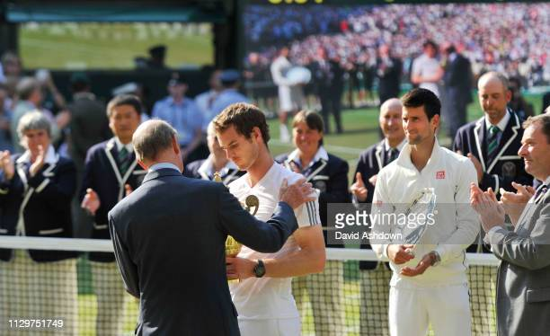 Andy Murray receives the trophy from the Duke of Kent with Novak Djokovic on his right with it on the bis TV screen behind after winning his 1st...
