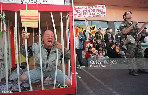 Andy Nguyen cries in a mock prison cage while demostrating against shop owner Truong Van Tran February 15 1999 who placed a Communist flag and a...
