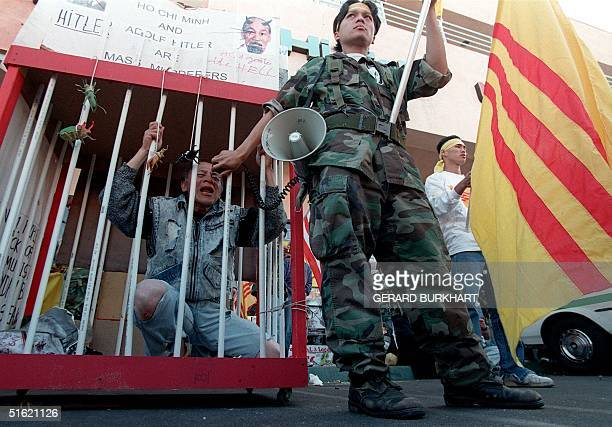Andy Nguyen occupies a makeshift cage with posters describing Ho Chi Minh and Adolf Hitler as mass murderers as Steven Nguyen holds a bullhorn for...