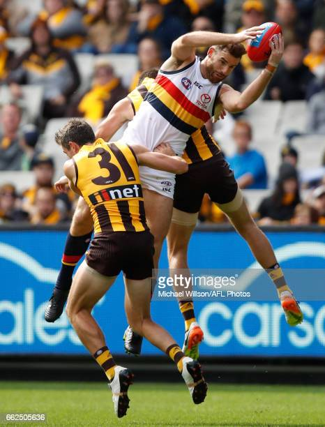 Andy Otten of the Crows marks over Ricky Henderson and Jack Gunston of the Hawks during the 2017 AFL round 02 match between the Hawthorn Hawks and...