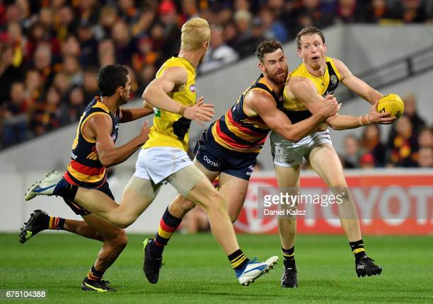 Andy Otten of the Crows tackles Dylan Grimes of the Tigers during the round six AFL match between the Adelaide Crows and the Richmond Tigers at...