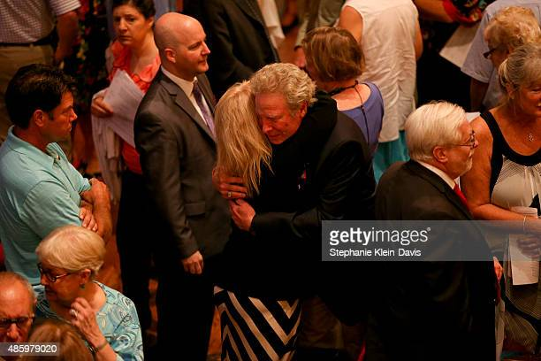 Andy Parker father of Alison Parker is comforted by a family member of Parker's boyfriend and colleague Chris Hurst following the Interfaith Service...