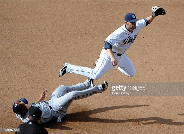 Andy Parrino of the San Diego Padres turns a double play as Alex Gonzalez of the Milwaukee Brewers slides into second base during the fourth inning...