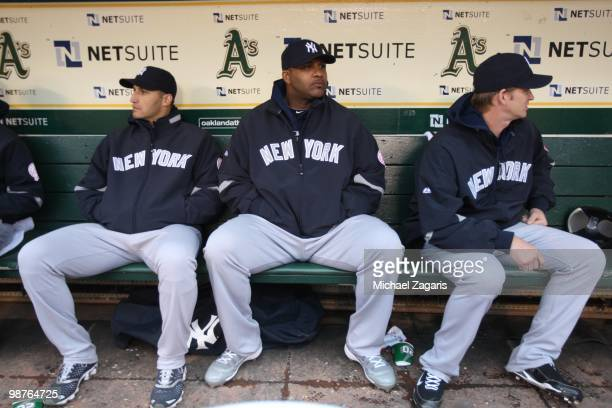 Andy Pettitte CC Sabathia and AJ Burnett of the New York Yankees sitting in the dugout prior to the game against the Oakland Athletics at the Oakland...