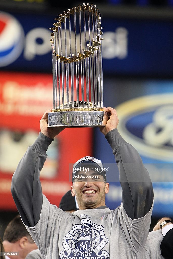 Andy Pettitte #46 of the New York Yankees celebrates with the trophy after their 7-3 win against the Philadelphia Phillies in Game Six of the 2009 MLB World Series at Yankee Stadium on November 4, 2009 in the Bronx borough of New York City.