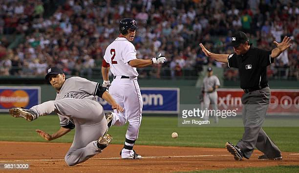 Andy Pettitte of the New York Yankees is tripped up covering first base as Jacoby Ellsbury of the Boston Red Sox reaches it safely in the first...