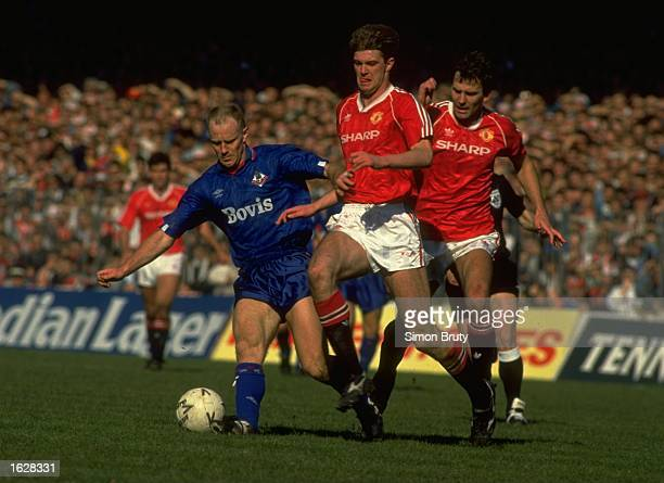 Andy Ritchie of Oldham is tackled by Gary Pallister and Bryan Robson both of Manchester United during the FA Cup SemiFinal at Maine Road in...