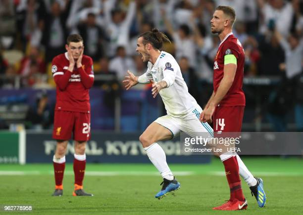 Andy Robertson and Jordan Henderson of Liverpool look dejected as Gareth Bale of Real Madrid celebrates scoring his side's third goal during the UEFA...