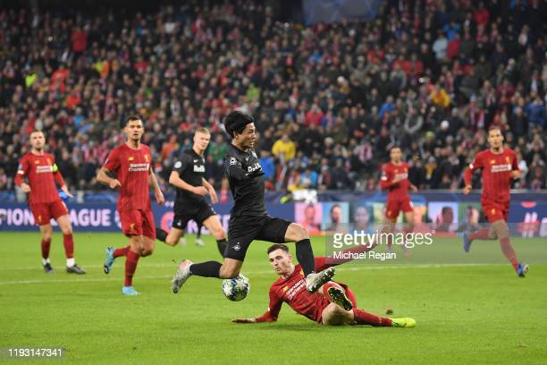 Andy Robertson of Liverpool tackles Takumi Minamino of Red Bull Salzburg during the UEFA Champions League group E match between RB Salzburg and...