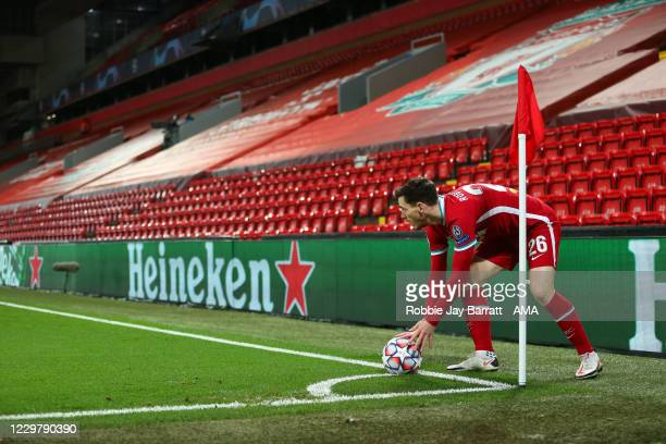 Andy Robertson of Liverpool takes a short corner in front of an empty stand with Heineken branding on the sponsor boards during the UEFA Champions...