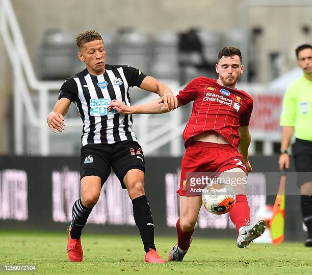 Andy Robertson of Liverpool with Dwight Gayle of Newcastle during the Premier League match between Newcastle United and Liverpool FC at St James Park...