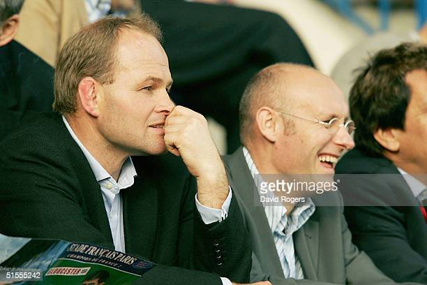 Andy Robinson the England Head Coach talks with the French National Coach Bernard Laporte during the Heineken Cup match between Stade Francais and...