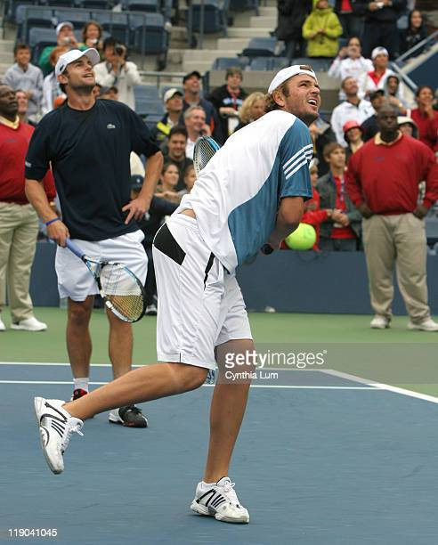 Andy Roddick and Mardy Fish hit balls to fans in the stands at Arthur Ashe Stadium during brief dry spell at the US Open, played at the USTA Billie...