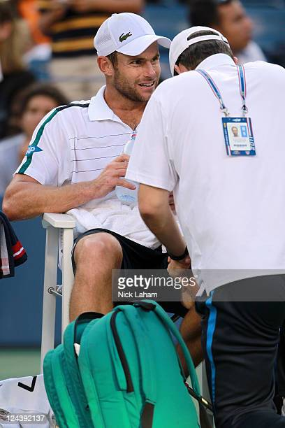 Andy Roddick of the United States gets worked on by a court trainer during a break in play against Rafael Nadal of Spain during Day Twelve of the...