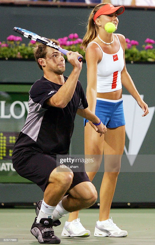 Andy Roddick of the United States hits a shot while holding the hand of Daniela Hantuchova of Slovakia during the ATP All-Star Rally for Relief at the Pacific Life Open at the Indian Wells Tennis Garden on March 11, 2005 in Indian Wells, California.