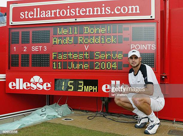 Andy Roddick of the USA poses next to the official scoreboard showing his world record serve speed after his victory over Lleyton Hewitt of Australia...