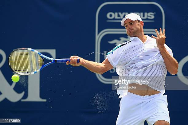 Andy Roddick of the USA returns a shot to John Isner of the USA during the semifinals of the WinstonSalem Open at the Wake Forest University Tennis...