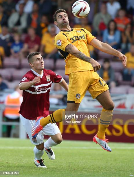 Andy Sandell of Newport County AFC controls the ball watched by Danny Emerton of Northampton Town during the Sky Bet League Two match between...
